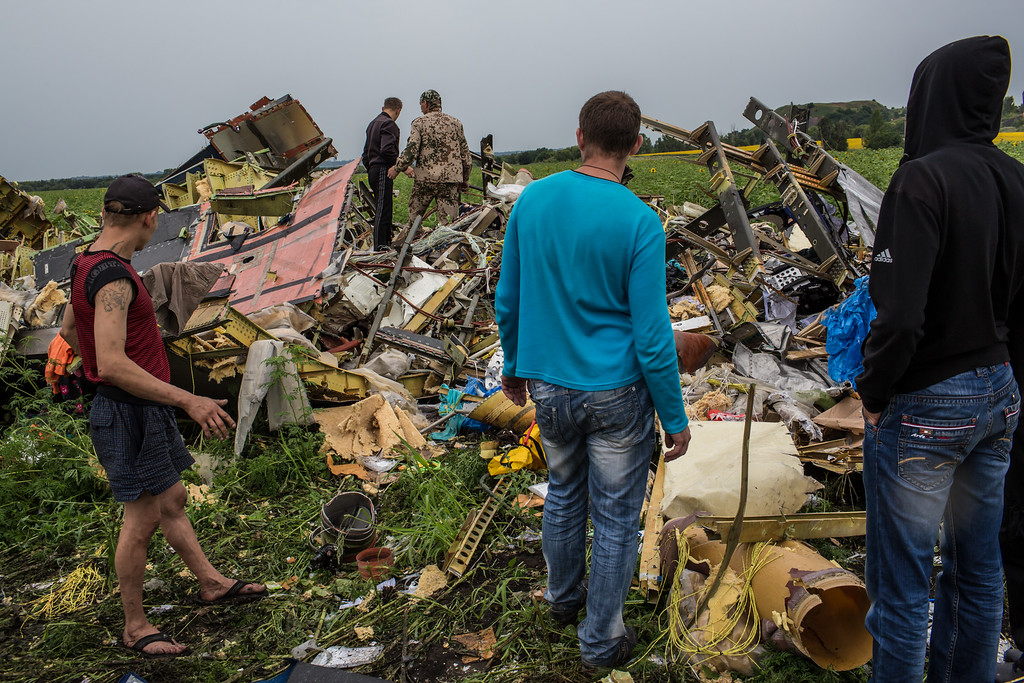. Men look at the wreckage of passenger plane Air Malaysia flight MH17 on July 18, 2014 in Grabovka, Ukraine. Air Malaysia flight MH17 traveling from Amsterdam to Kuala Lumpur crashed yesterday on the Ukraine/Russia border near the town of Shaktersk. The Boeing 777 was carrying 298 people including crew members, the majority of the passengers being Dutch nationals, believed to be at least 173, 44 Malaysians, 27 Australians, 12 Indonesians and 9 Britons.   (Photo by Brendan Hoffman/Getty Images)