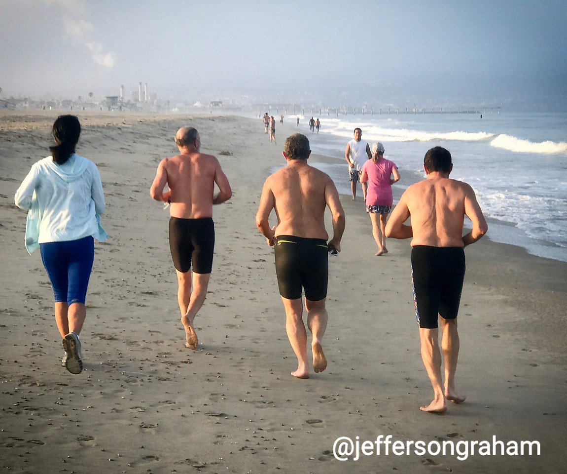 A group of runners enjoying a morning jog on Manhattan Beach sands, heading towards Hermosa Beach
