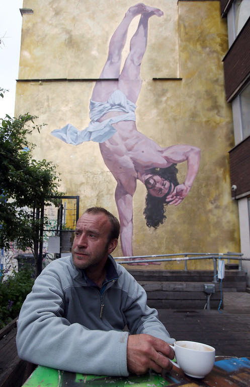 . Artist Cosmo Sarson sits besides a giant mural of Jesus breakdancing that he has painted on the 8.5 metre wall beside The Canteen in Stokes Croft and is being officially unveiled this evening, on June 11, 2012 in Bristol, England. The artist was commissioned by The Canteen to paint the wall, which is directly opposite Banksy\'s Mild Mild West. The controversial \'Breakdancing Jesus\', which took 4 days to paint and involved a kilo of glitter and was inspired by an actual event in the Vatican where breakdancers performed to an applauding Pope John Paul II in 2004, is likely to be the latest attraction for graffiti tourists visiting Bristol, often seen the spiritual home of underground artist Banksy. (Photo by Matt Cardy/Getty Images)