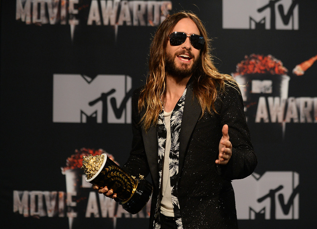 """. Jared Leto poses in the press room with the award for Best On-Screen Transformation for \""""Dallas Buyers Club\"""" at the MTV Movie Awards on Sunday, April 13, 2014, at Nokia Theatre in Los Angeles. (Photo by Jordan Strauss/Invision/AP)"""