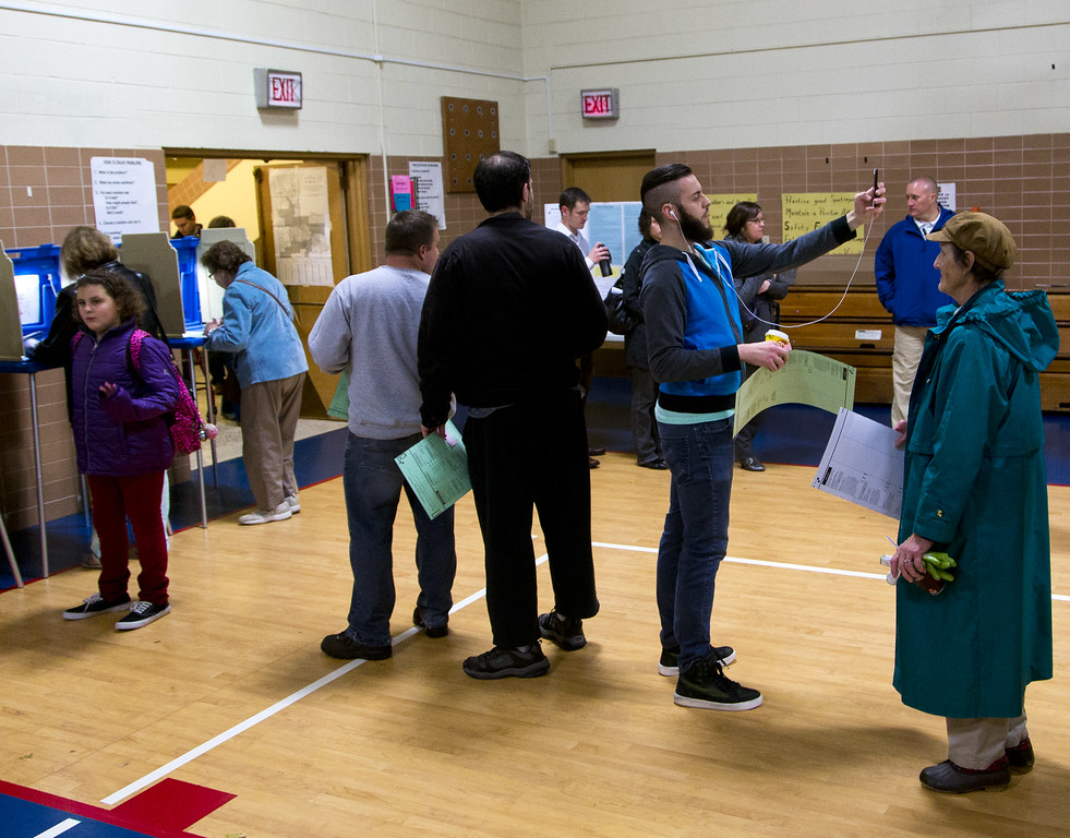 """. A man takes a \""""selfie\"""" as he waits in line to cast his vote in the Wisconsin gubernatorial race between Republican incumbent Scott Walker and Democratic gubernatorial challenger Mary Burke on election day at Jefferson Elementary School, November 4, 2014 in Milwaukee, Wisconsin. Walker is running in a tight race against opponent Mary Burke. (Photo by Darren Hauck/Getty Images)"""