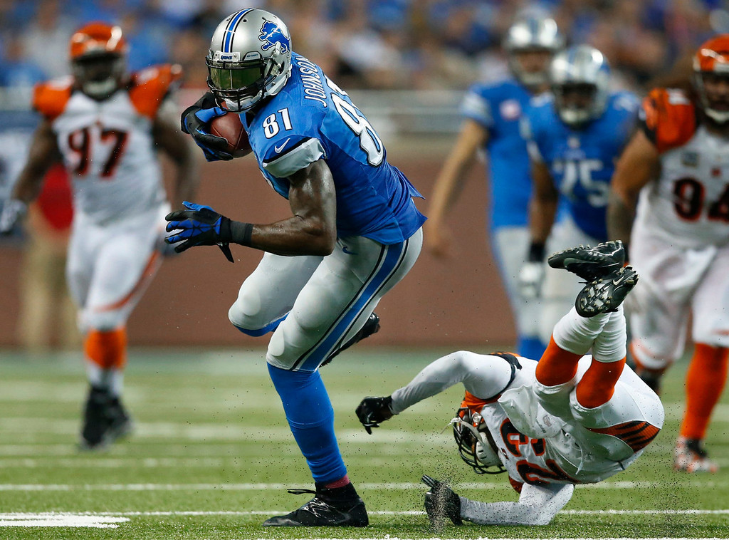 . Detroit Lions wide receiver Calvin Johnson (81) avoids the tackle of Cincinnati Bengals cornerback Terence Newman (23) in the first quarter of an NFL football game against Sunday, Oct. 20, 2013, in Detroit. (AP Photo/Rick Osentoski)