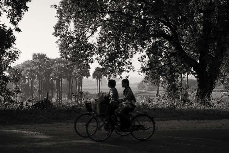 Two women cycling from work in the late afternoon.  Myanmar 20017.