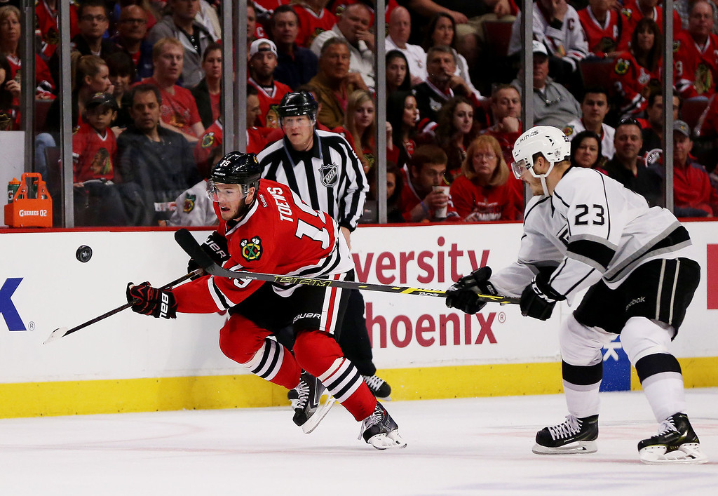 . Jonathan Toews #19 of the Chicago Blackhawks controls the puck against Dustin Brown #23 of the Los Angeles Kings in the second period of Game One of the Western Conference Final during the 2014 Stanley Cup Playoffs at United Center on May 18, 2014 in Chicago, Illinois.  (Photo by Jonathan Daniel/Getty Images)