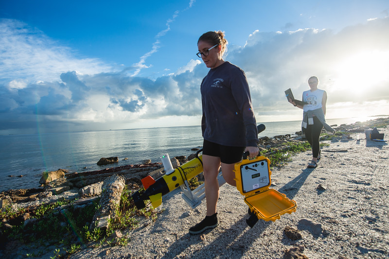 Emily Cira (left) and Jessica Tolan, both research technicians working under the direction of Dr. Wetz, prepare for the release of an ECO Mapper, an autonomous underwater vehicle (AUV) used to survey bodies of water.