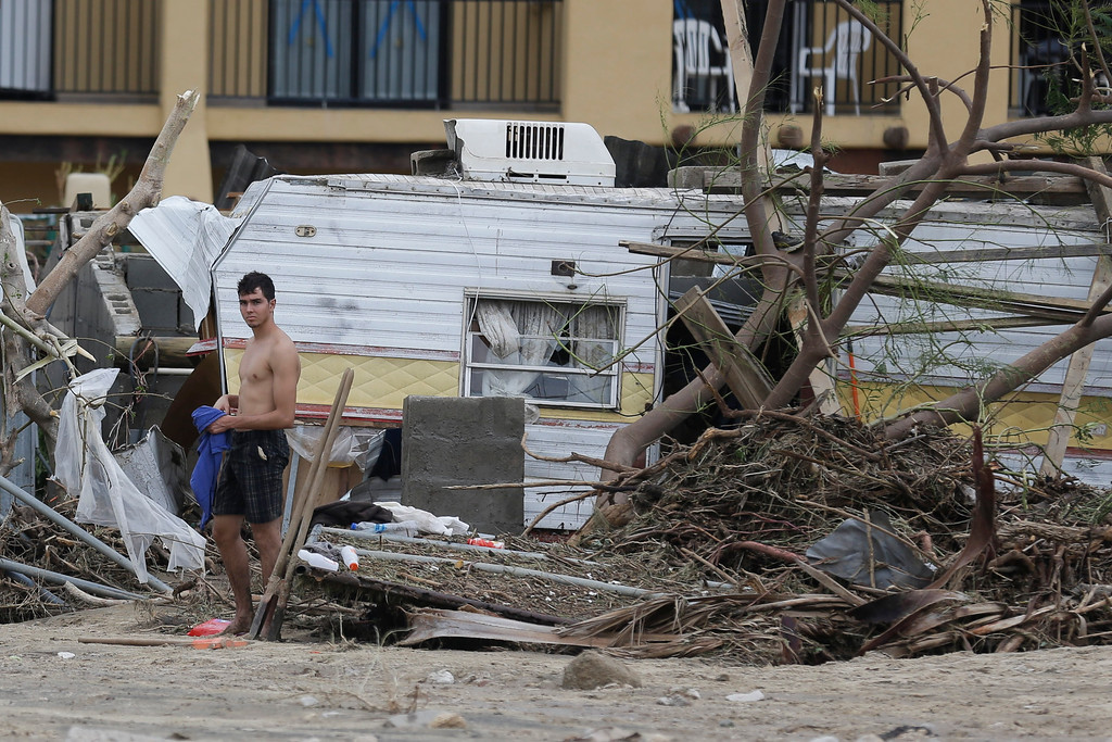 . A man stands by a trailer that was swept along with debris, by the flood waters and high winds of Hurricane Odile in Los Cabos, Mexico, Monday, Sept. 15, 2014. (AP Photo/Victor R. Caivano)