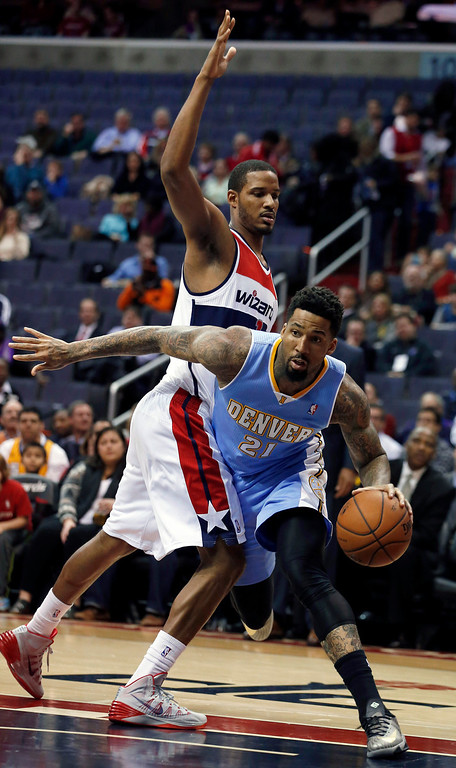 . Denver Nuggets forward Wilson Chandler (21) drives around Washington Wizards forward Trevor Ariza, left, in the first half of an NBA basketball game on Monday, Dec. 9, 2013, in Washington. (AP Photo/Alex Brandon)
