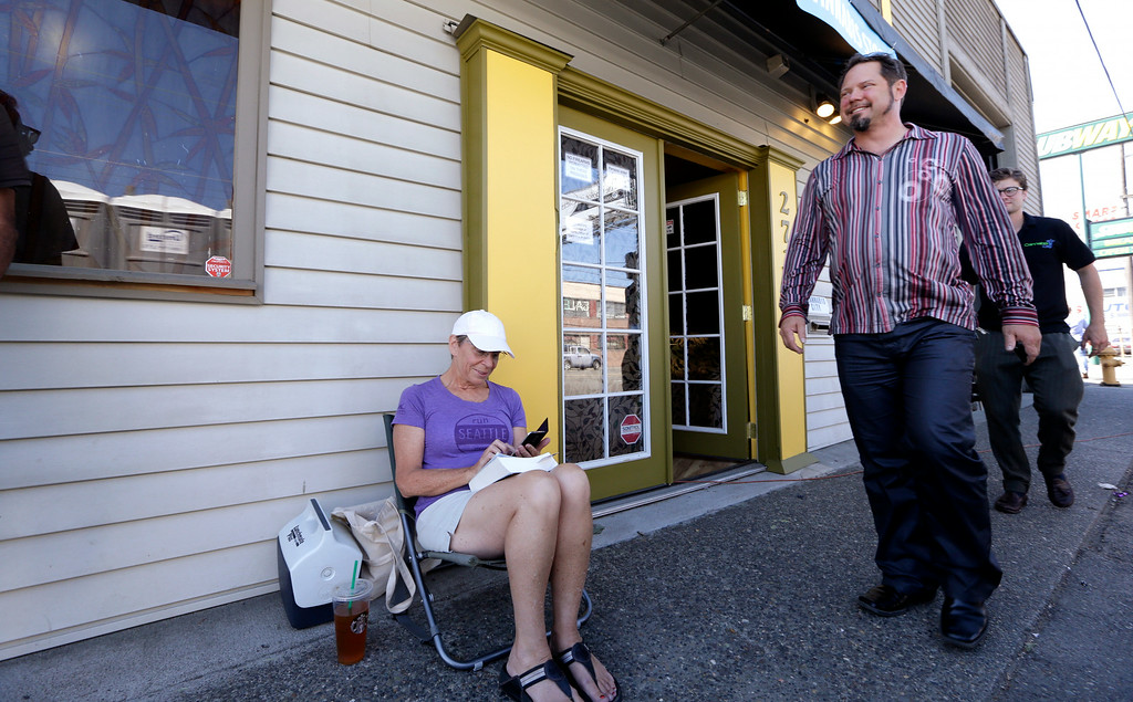 . Cannabis City owner James Lathrop, right, walks past first-in-line customer Deb Greene at the recreational marijuana store Monday, July 7, 2014, in Seattle. The store will be the first and, initially, only store in Seattle to legally sell recreational pot when sales begin Tuesday. (AP Photo/Elaine Thompson)