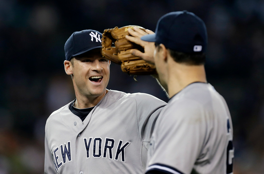 . New York Yankees third baseman Chase Headley, left, is congratulated by first baseman Mark Teixeira after making an out against the Detroit Tigers in the third inning of a baseball game in Detroit Tuesday, Aug. 26, 2014. (AP Photo/Paul Sancya)