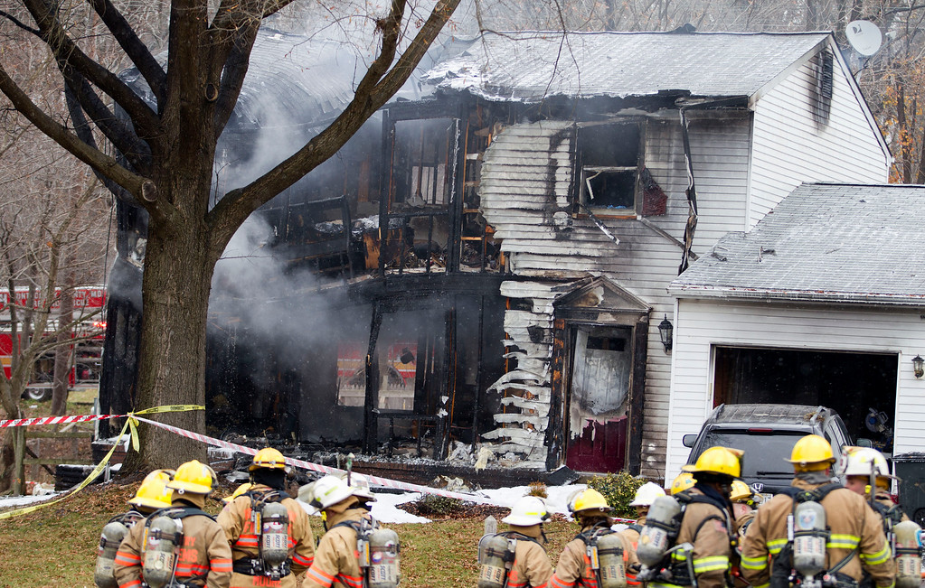 . Montgomery County, Md., firefighters stand outside a house where a small private jet crashed in Gaithersburg, Md., Monday, Dec. 8, 2014. A woman and her two young sons inside the home and three people on the aircraft were killed, authorities said. (AP Photo/Jose Luis Magana)