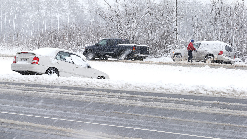 . People work to get a vehicle out of the snow along Route 60 in Midlothian, Va. on  Wednesday, March 6, 2013.  A winter storm marched into the Mid-Atlantic region Wednesday, dumping more than a foot of snow in some places and knocking out power to nearly 200,000 homes.  (AP Photo/Richmond Times-Dispatch, Alexa Welch Edlund).