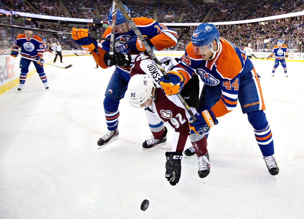 . Colorado Avalanche\'s Gabriel Landeskog (92) is checked off the puck by Edmonton Oilers\' Justin Schultz (19) and Corey Potter (44) during first-period NHL hockey game action in Edmonton, Alberta, Thursday, Dec. 5, 2013. (AP Photo/The Canadian Press, Jason Franson)