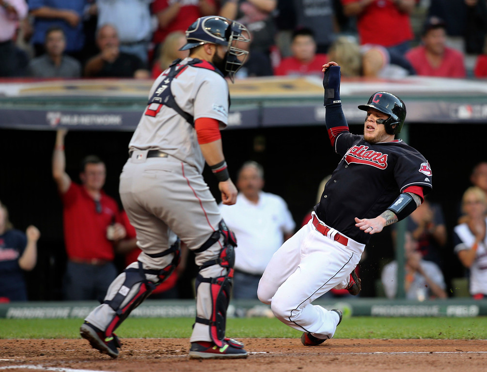 . Cleveland Indians\' Roberto Perez slides safely into home plate on a Jason Kipnis single as Boston Red Sox catcher Sandy Leon waits for the throw during the fourth inning of Game 2 of a baseball American League Division Series, Friday, Oct. 7, 2016, in Cleveland. (AP Photo/Aaron Josefczyk)