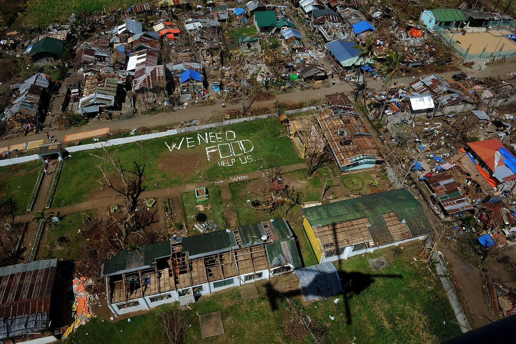 ". An aerial photo shows a message that reads ""We Need Food Help Us\"" amongst the devastation in the aftermath of typhoon Haiyan in Ormoc, on the eastern island of Leyte on November 18, 2013. Philippine President Benigno Aquino on November 18 blamed the slow response to the ravages of Typhoon Haiyan on the total collapse of local government in the face of the storm\'s unprecedented destructive power. NOEL CELIS/AFP/Getty Images"