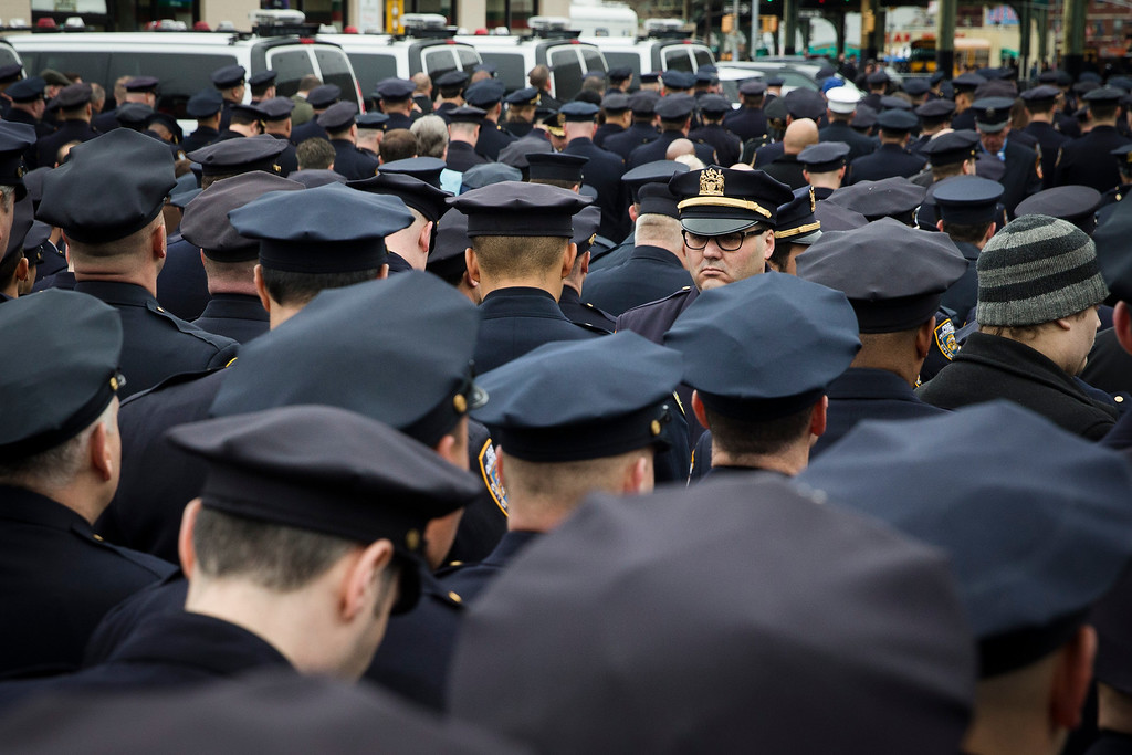 . A lone police officer stands front as other colleagues turn their backs while Mayor Bill de Blasio speaks during the funeral of New York Police Department Officer Wenjian Liu at Aievoli Funeral Home, Sunday, Jan. 4, 2015, in the Brooklyn borough of New York. Liu and his partner, officer Rafael Ramos, were killed Dec. 20 as they sat in their patrol car on a Brooklyn street. The shooter, Ismaaiyl Brinsley, later killed himself. (AP Photo/John Minchillo)