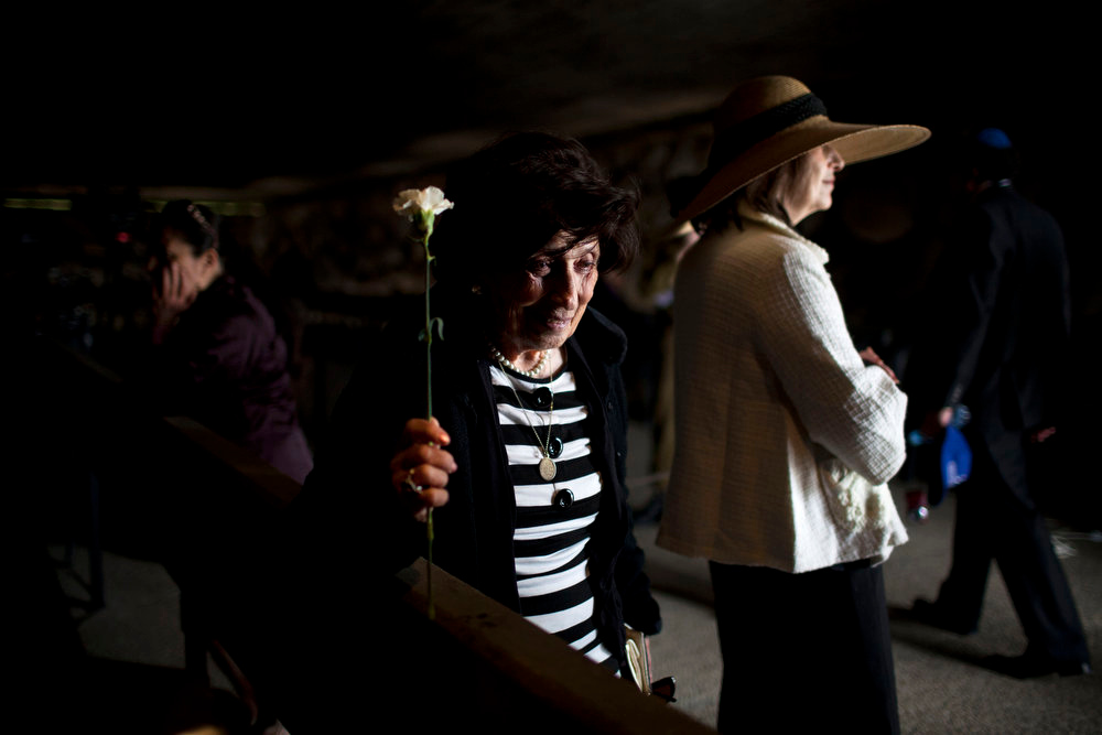 Description of . A Holocaust survivor holds a flower during a ceremony marking the annual Holocaust Remembrance Day at the Yad Vashem Holocaust Memorial in Jerusalem on Monday, April 8, 2013. Israel came to a standstill for two mournful minutes Monday as sirens pierced the air in an annual ritual to remember the 6 million Jews systematically murdered by German Nazis and their collaborators during the Holocaust in World War II. (AP Photo/Oded Balilty)