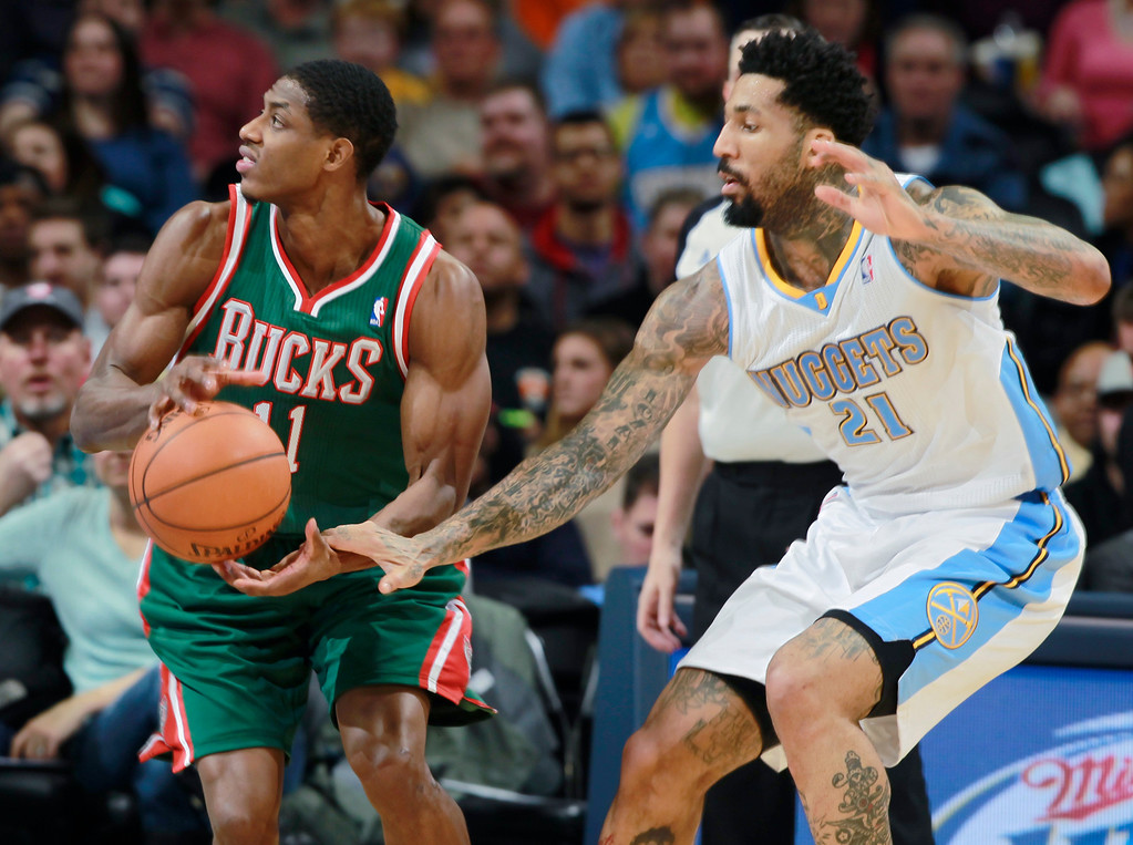 . Denver Nuggets forward Wilson Chandler, right, tries to steal ball from Milwaukee Bucks guard Brandon Knight in the third quarter of the Nuggets\' 110-100 victory in an NBA basketball game in Denver on Wednesday, Feb. 5, 2014. (AP Photo/David Zalubowski)