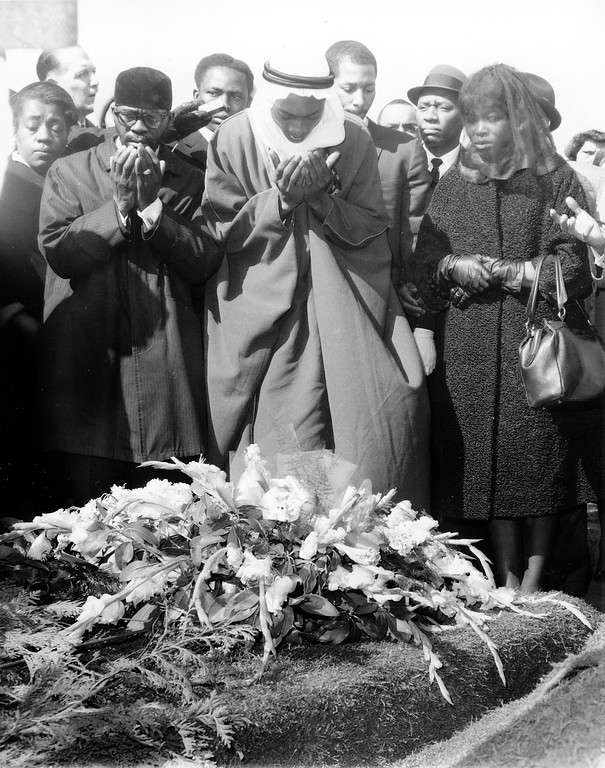 . GRAVESIDE PRAYERS FOR MALCOLM X --- Imam Alhajj Heshaans Jaaber, in Arab robes, chants the Talqueen and other Islamic prayers for Malcolm X at the graveside of the slain Black Nationalist leader. Funeral director Joseph Hall is left and Malcolm\'s Widow, Betty, at right. The cemetery is Ferncliffe at Hartsdale, Westchester County, N.Y. Funeral services were held earlier February 27, 1965 in New York\'s Harlem. (AP PHOTO/stf)