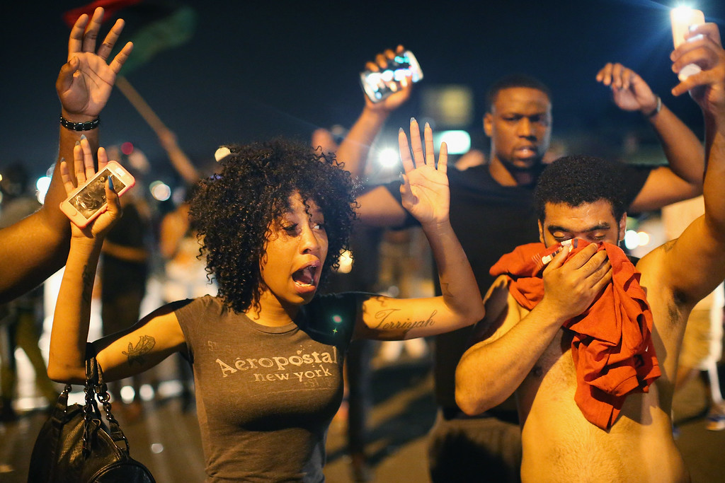 . Demonstrators protesting the killing of teenager Michael Brown by a Ferguson police officer try to stand their ground despite being overcome by tear gas on  August 17, 2014 in Ferguson, Missouri. Despite the Brown family\'s continued call for peaceful demonstrations, violent protests have erupted nearly every night in Ferguson since his death.  (Photo by Scott Olson/Getty Images)