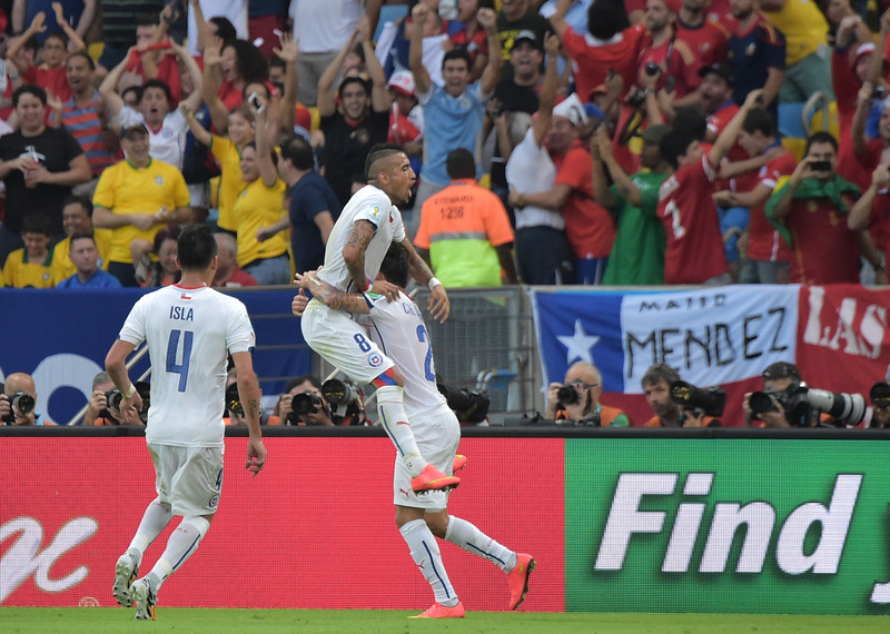 . Chile\'s midfielder Charles Aranguiz (R) celebrates with his temmate Chile\'s midfielder Arturo Vidal after scoring a goal during a Group B football match between Spain and Chile in the Maracana Stadium in Rio de Janeiro during the 2014 FIFA World Cup on June 18, 2014.  (GABRIEL BOUYS/AFP/Getty Images)