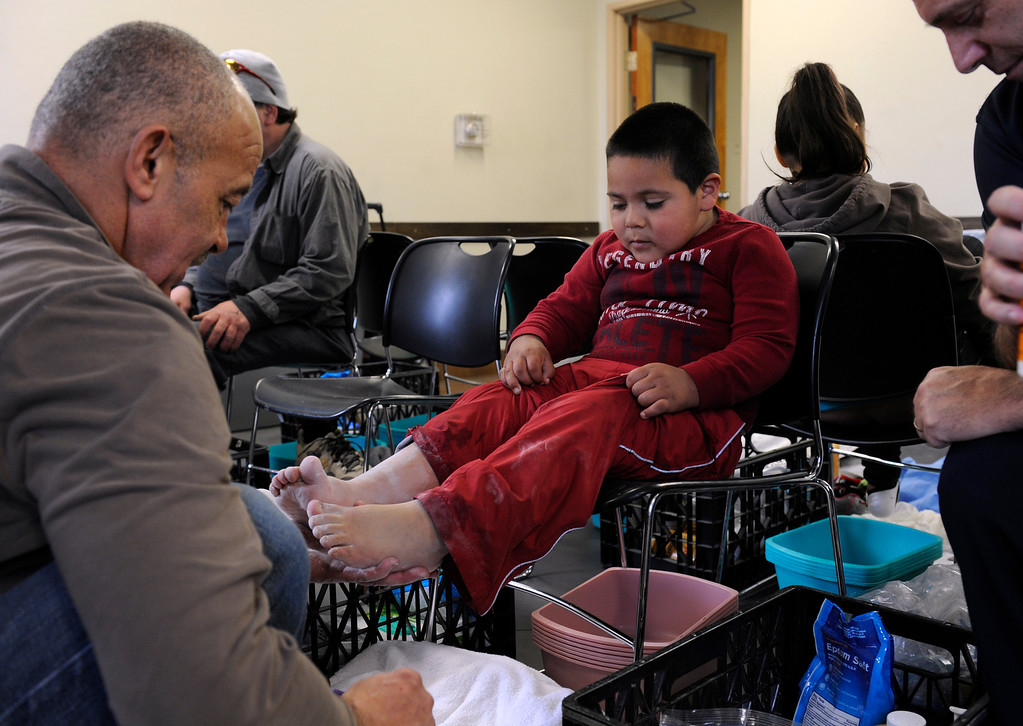 . DEVNER, CO.- MARCH 29: Dery Oropeza, 4, holds still so volunteer Melvin Bush, left, can dry his feet. The Denver Rescue Mission partners with Volunteers of American and Runner\'s Roost to supply approximately 600 homeless adults and children with a new pair of shoes, sock and an Easter meal at the 20th Annual Easter Celebration  at the Rescue Mission on Lawrence Street. Many of the homeless had their feet washed by volunteers, symbolic of the part of the Christian tradition, mirroring Jesus\' washing of his disciples\' feet.(Photo By Kathryn Scott Osler/The Denver Post)