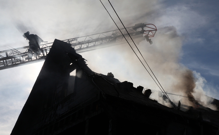 . It took Oakland firefighters over an hour to battle a fully involved house fire at a three-story wood-frame house in the 2000 block of East 26th Street that started about 9 a.m. in Oakland, Calif., on Tuesday, Jan. 15, 2013.  Besides flames and smoke in the home\'s attic, firefighters were hampered by a large amount of personal belongings inside the home and a fallen power line on the side of the house, fire officials said.(Laura A. Oda/Staff)
