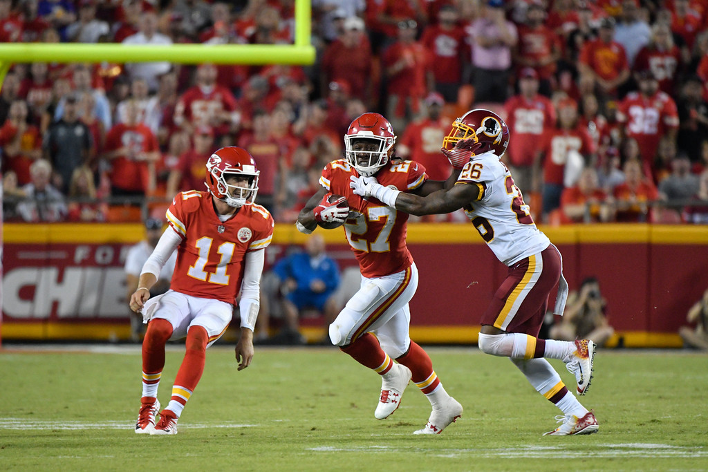 . Kansas City Chiefs running back Kareem Hunt (27) is tackled by Washington Redskins cornerback Bashaud Breeland (26) as Kansas City Chiefs quarterback Alex Smith (11) looks on, during the second half of an NFL football game in Kansas City, Mo., Monday, Oct. 2, 2017. (AP Photo/Ed Zurga)