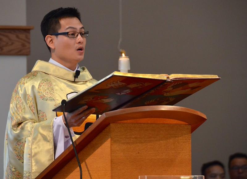 Fr. Joseph reads the Gospel in English following the Vietnamese