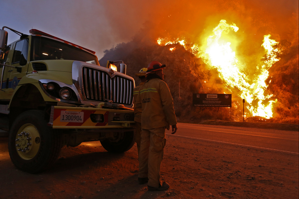 . Firefighters monitor the Colby Fire burning for a second day on a hillside on Highway 39 in Azusa, California, January 17. Three men have been arrested and charged with starting the fire that has now destroyed 1,700 acres of land and several homes around Glendora and Azusa in the San Gabriel Valley, prompting officials to order evacuations for houses near the fire. (Photo by Jonathan Alcorn/Getty Images)