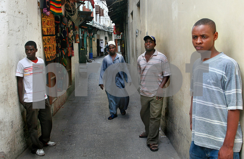 Young dark-skinned Africans stand near walls houses in Stone Town. istock