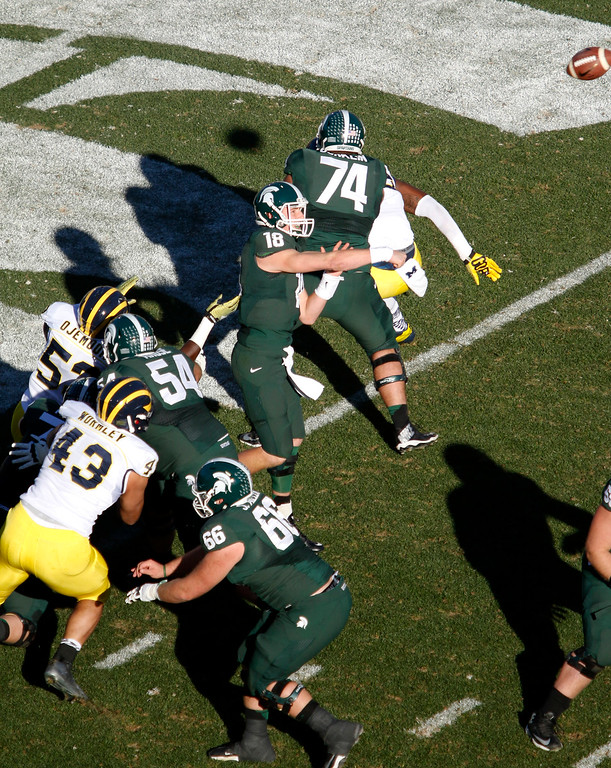 . Michigan State quarterback Connor Cook (18) throws a pass as teammates Jack Conklin (74), Connor Kruse (54) and Jack Allen (66) block against Michigan\'s Chris Wormley (43) and Mario Ojemudia (53) during the second quarter of an NCAA college football game, Saturday, Oct. 25, 2014, in East Lansing, Mich. (AP Photo/Al Goldis)