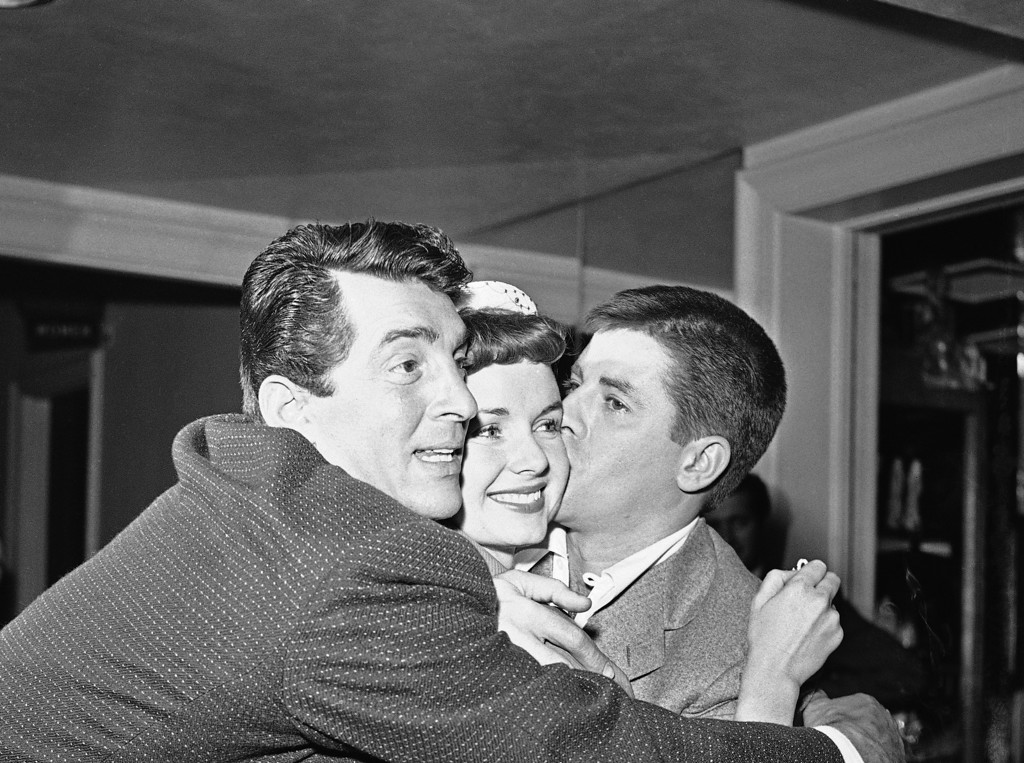 ". Dean Martin, Debbie Reynolds and Jerry Lewis, left to right, embrace each other upon acknowledging the news that they were voted the ""Most Cooperative Stars of 1954\"" by the Hollywood Women\'s Press Club, Dec. 28, 1954. (AP Photo)"