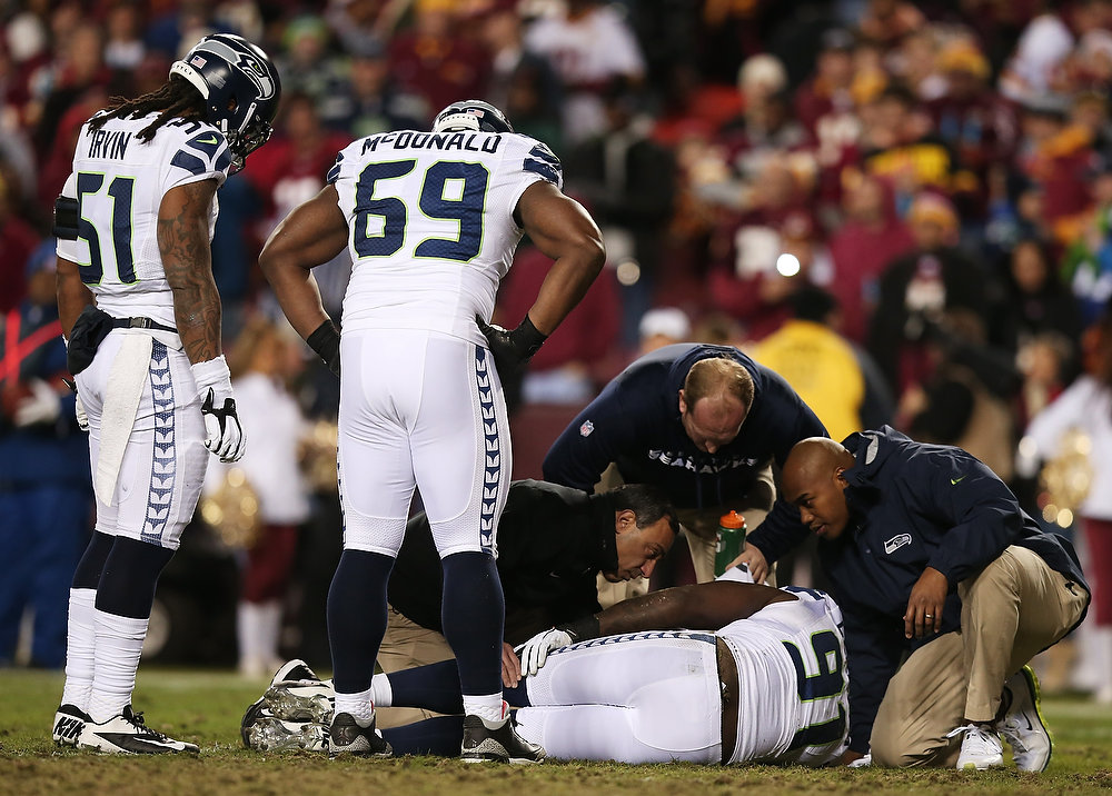 Description of . Chris Clemons #91 of the Seattle Seahawks receives medical attention after being injured on a third quarter play against the Washington Redskins during the NFC Wild Card Playoff Game at FedExField on January 6, 2013 in Landover, Maryland.  (Photo by Win McNamee/Getty Images)