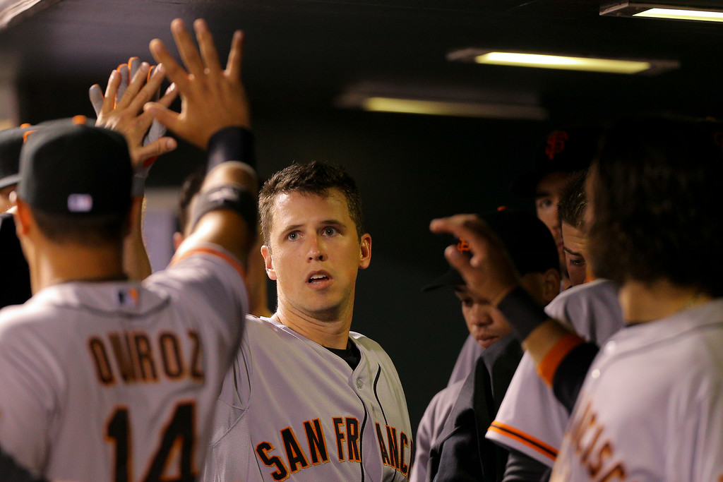 . DENVER, CO - SEPTEMBER 2:  Buster Posey #28 of the San Francisco Giants is congratulated in the dugout after hitting a solo home run during the sixth inning against the Colorado Rockies at Coors Field on September 2, 2014 in Denver, Colorado. (Photo by Justin Edmonds/Getty Images)