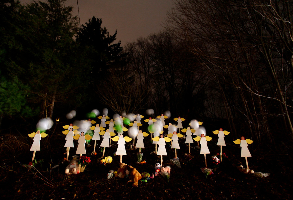. Twenty-seven wood painted angels are displayed outside of a home to honor the victims killed at Sandy Hook Elementary School in Newtown, Connecticut December 16, 2012. Twelve girls, eight boys and six adult women were killed in the shooting on Friday at Sandy Hook Elementary School in Newtown. REUTERS/Joshua Lott