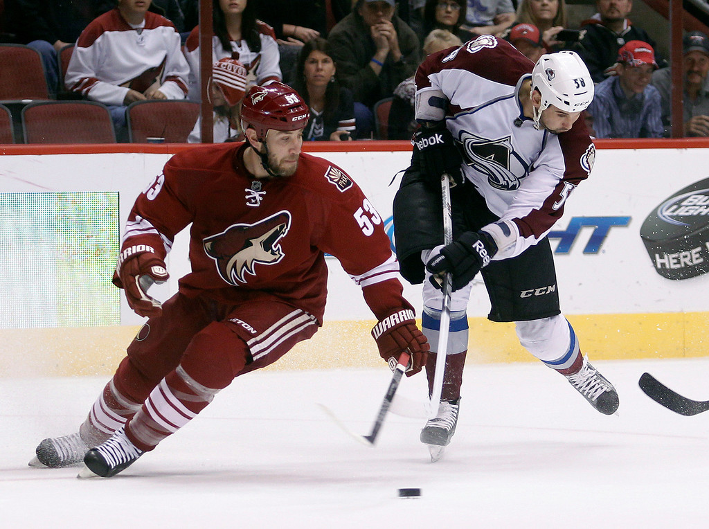 . Colorado Avalanche left winger Patrick Bordeleau, right, attempts a shot as Phoenix Coyotes defenseman Derek Morris, left, spins around to defend in the first period of NHL hockey game, Saturday, April 6, 2013, in Glendale, Ariz. (AP Photo/Paul Connors)