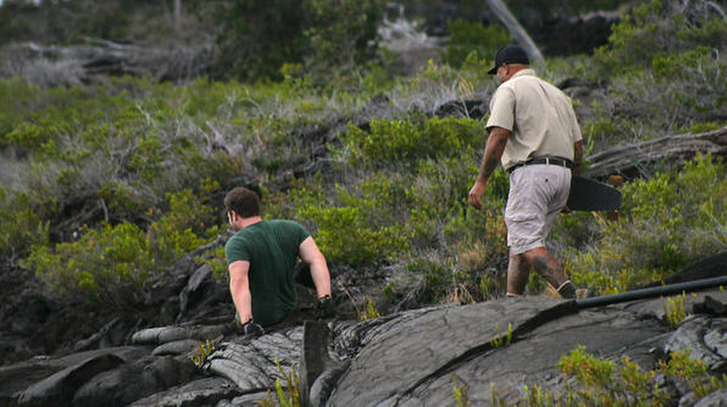 . Kevin and Warren walk over the lava rocks in Hawaii to check out the terrain before Kevin takes his mountain board on a ride.