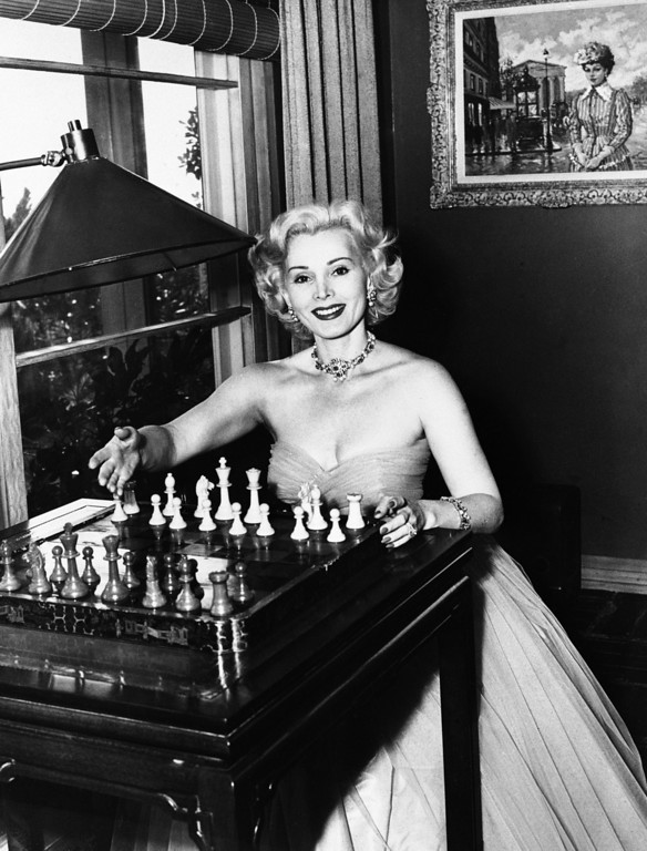 ". Zsa Zsa Gabor in working on  1952 film,  ""Moulin Rouge\"" directed by John Huston.   Gabor  sits at the chess table, ready for a game with her husband, George Sanders.  (AP Photo)"