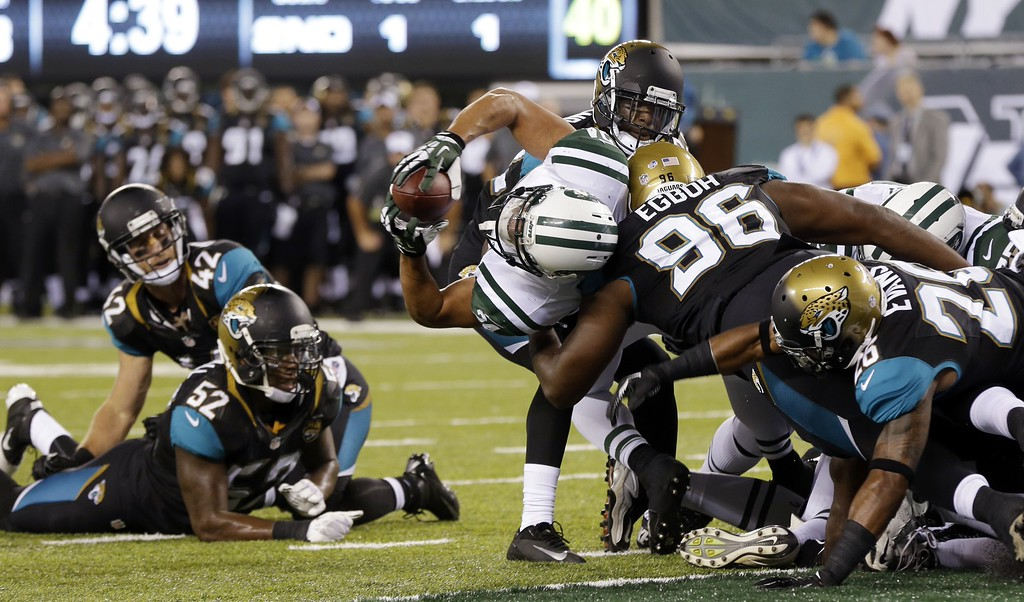 . Jacksonville Jaguars defensive end Pannel Egboh (96) is unable to stop New York Jets running back Kahlil Bell, center, as he breaks the plane for a touchdown during the second half of an NFL preseason football game, Saturday, Aug. 17, 2013, in East Rutherford, N.J. (AP Photo/Seth Wenig)