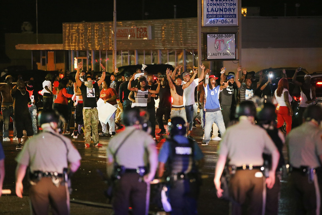 . FERGUSON, MO - AUGUST 15: Demonstrators taunt police during a protest over the shooting death of Michael Williams on August 15, 2014 in Ferguson, Missouri, Police shot pepper spray,  smoke, gas and flash grenades at protestors before retreating. Several businesses were looted as the county police sat nearby with armored personnel carriers (APC). Violent outbreaks have taken place in Ferguson since the shooting death of Brown by a Ferguson police officer on August 9.  (Photo by Scott Olson/Getty Images)