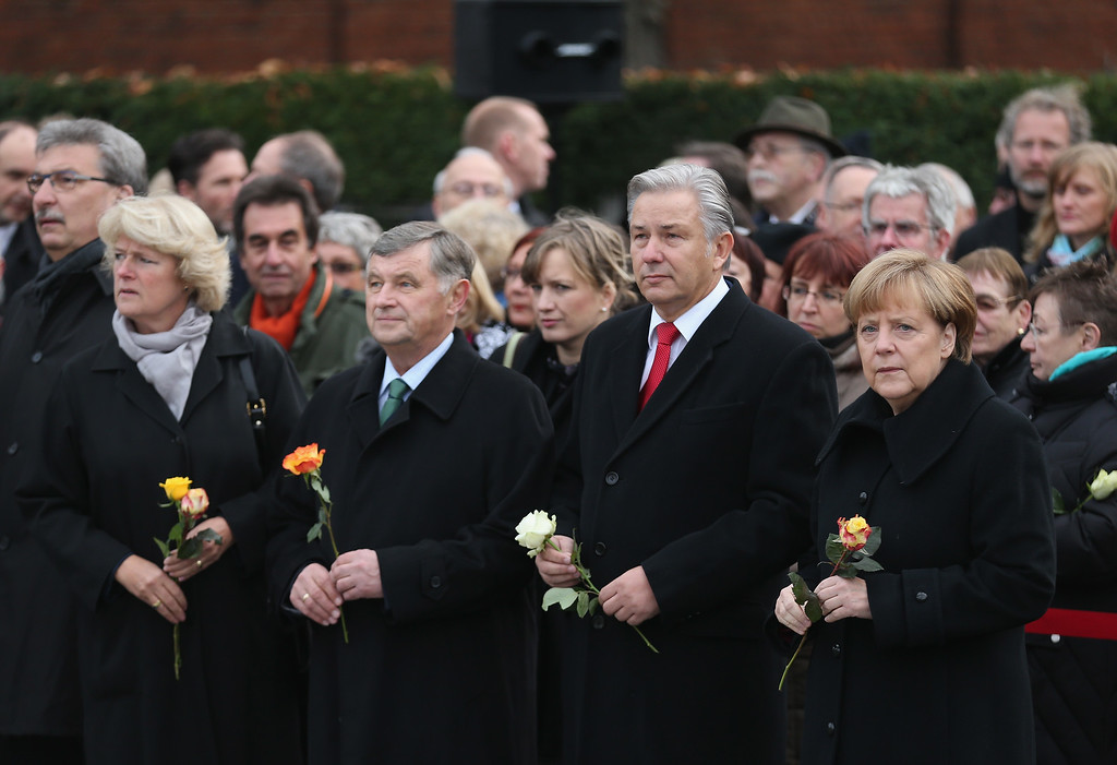. BERLIN, GERMANY - NOVEMBER 09:  (From L to R) German Commissioner for Culture Monika Gruetters, former Hungarian Prime Minister Miklos Nemeth, Berlin Mayor Klaus Wowereit and German Chancellor Angela Merkel arrive to lay flowers at the Berlin Wall Memorial at Bernauer Strasse on the 25th anniversary of the fall of the Wall on November 9, 2014 in Berlin, Germany. The city of Berlin is commemorating the 25th anniversary of the fall of the Berlin Wall with an installation of 6,800 lamps coupled with illuminated balloons along a 15km route where the Wall once ran and divided the city into capitalist West and communist East. The fall of the Wall on November 9, 1989, was among the most powerful symbols of the revolutions that swept through the communist countries of Eastern Europe and heralded the end of the Cold War. Built by the communist authorities of East Germany in 1961, the Wall prevented East Germans from fleeing west and was equipped with guard towers and deadly traps.  (Photo by Sean Gallup/Getty Images)