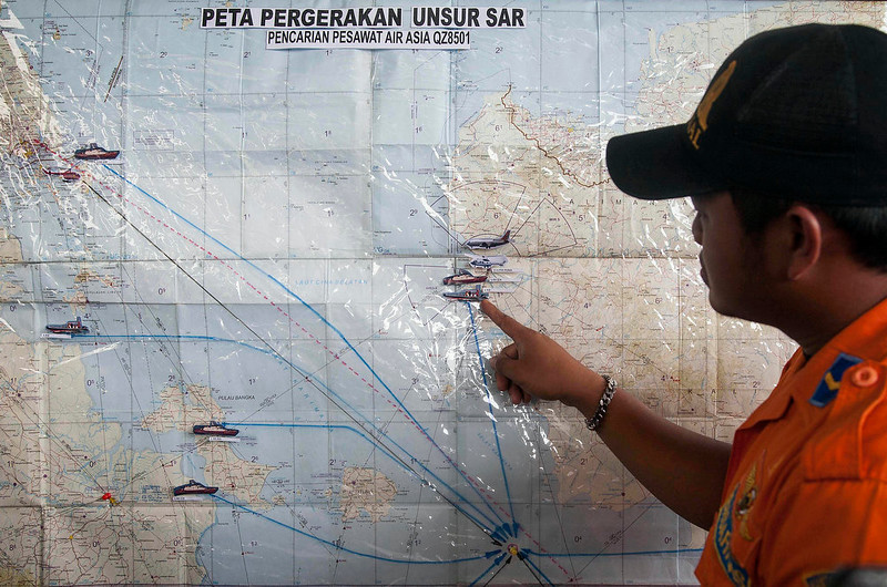 . A search and rescue officer points to a co-ordination map of Indonesia at the crisis center set up by local authorities in search of the missing AirAsia flight QZ8501 at Juanda International Airport in Surabaya, East Java, Indonesia, Monday, Dec. 29, 2014. Search planes and ships from several countries on Monday were scouring Indonesian waters over which the AirAsia jet disappeared, more than a day into the region\'s latest aviation mystery. Flight 8501 vanished Sunday in airspace thick with storm clouds on its way from Surabaya, Indonesia, to Singapore. (AP Photo/Trisnadi Marjan)