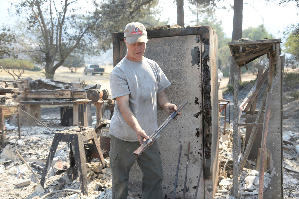 . World famous gun maker Lon Paul looks over of whats left of his rifle gun shop in Mountain Center California, during the Mountain Fire near Idyllwild, California July 18, 2013. The blaze erupted on Monday afternoon about 100 miles (161 km) east of Los Angeles in the scenic but rugged San Jacinto Mountains that overlook Palm Springs, Rancho Mirage and several smaller desert towns.  Photo by Gene Blevins/LA Dailynews