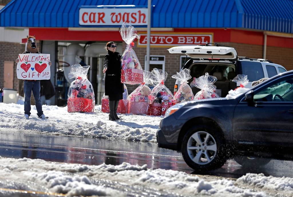 . Nina McMillan, right, and her son Justin McMillon, left, try to catch drivers\' attention as they sell Valentine\'s Day basket on the side of a street in Charlotte, N.C., Friday, Feb. 14, 2014. Residents are digging out from one of the worst winter storms in many years. (AP Photo/Chuck Burton)