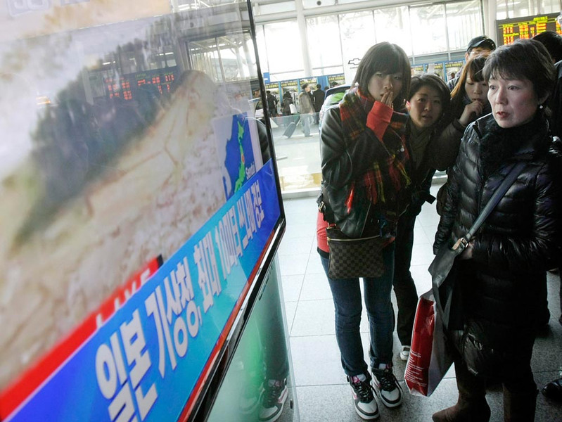 ". Japanese tourists watch a TV news program about a strong earthquake hitting their country at Seoul Railway Station in Seoul, South Korea, Friday, March 11, 2011. The letters read ""Japan Meteorological Agency warns a tsunami.\"" (AP Photo/Ahn Young-joon)"