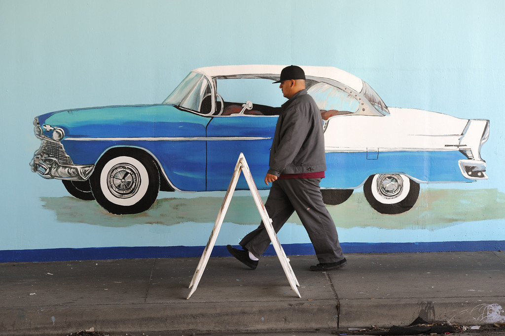 """. A person walks by the restored mural \""""Panorama: G.M. Recollections from the Past,\"""" on Van Nuys Boulevard in Panorama City. (Michael Owen Baker/Staff Photographer)"""