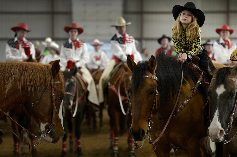 . Rachel Garrison rests her arms on her horse Turbo during the Easter church service inside the Jefferson County Fairgrounds horse arena on March 31, 2013.  A couple hundred of Jefferson county\'s Westernaires and local horsemen and women took part in the Jefferson County Horseman\'s annual Easter Parade annual that has been taking place in Jefferson County since World War II.  The riders, all on horseback, began their parade near 6th and Kipling, at 10301 West 6th ave,  and finished at the Jefferson County Fairgrounds almost  four miles away.    After the parade a church service, led by Pastor Ed Shirley of Mountain High Christian Church, was held in the horse arena on the fairgrounds. The Westernaires are a horse mounted precision drill organization of Jefferson County that was founded in 1949.  (Photo By Helen H. Richardson/ The Denver Post)