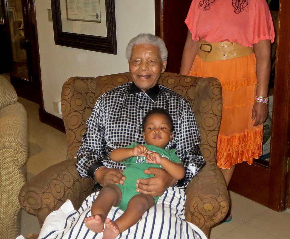 ". In this photo from Saturday Feb. 2, 2013, Nelson Mandela, 95, sits holding his great grandson Zen Manaway, 1, at home in Johannesburg, South Africa.  Zen, the youngest in the Mandela family, is traveling in the U.S. with his mother Zaziwe Dlamini-Manaway and his aunt Swati Dlamini, as the sisters promote their new reality TV series ""Being Mandela,\"" produced by COZI TV for NBC. The 30-minute weekly show premieres on Sunday, Feb. 10 at 9 p.m. EST and will follow the next generation of Mandela family through the experiences of sisters Zaziwe and Swati and their families. (AP Photo/Family Photo Courtesy of Being Mandela/COZI TV)"