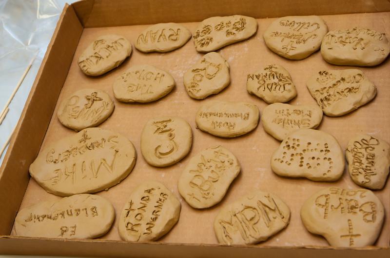 Founding Members writing on stones.