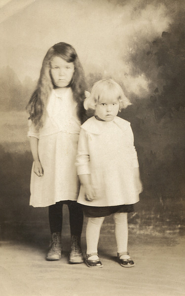 """Studio portrait of young sisters. On the back is written: """"Olive and Ruby Doss"""""""